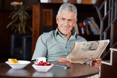 Homem superior no café da manhã com jornal imagem de stock