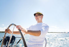 Homem superior no leme na navigação do barco ou do iate no mar Imagem de Stock