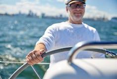 Homem superior no leme na navigação do barco ou do iate no mar fotografia de stock royalty free