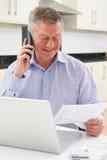 Homem superior no telefone que verifica finanças pessoais Fotografia de Stock