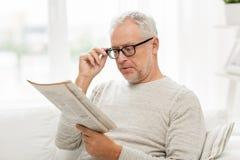 Homem superior nos vidros que lê o jornal em casa fotos de stock royalty free