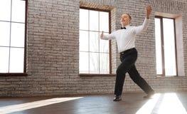 Homem superior otimista que executa a dança clássica no salão de baile Foto de Stock Royalty Free