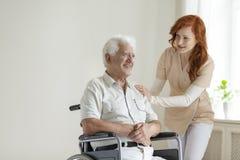 Homem superior paralizado de sorriso de apoio da enfermeira amigável no whee fotos de stock
