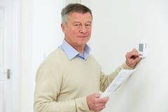 Homem superior preocupado com Bill Turning Down Heating Thermostat imagem de stock royalty free