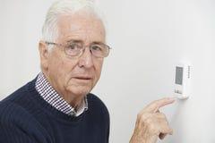 Homem superior preocupado que gira para baixo o termostato do aquecimento central Imagens de Stock