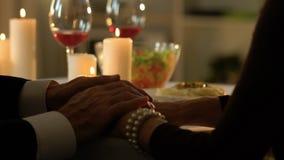Homem superior que afaga delicadamente as mãos fêmeas, data romântica no restaurante, close up video estoque