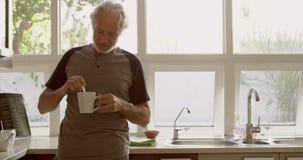 Homem superior que agita o café na cozinha 4k filme