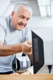 Homem superior que ajuda ao colega em usar o computador Foto de Stock Royalty Free