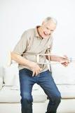 Homem superior que balança com muletas de Air Guitar Fotografia de Stock Royalty Free