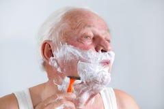 Homem superior que barbeia sua barba Fotos de Stock Royalty Free