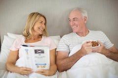Homem superior que come o café da manhã na cama Imagem de Stock Royalty Free