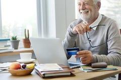 Homem superior que compra em linha com um cartão de crédito fotos de stock