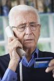 Homem superior que dá detalhes do cartão de crédito no telefone imagem de stock