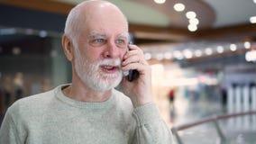 Homem superior que está no sorriso do shopping Usando seu smartphone, conversando com amigos ou família video estoque