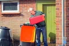 Homem superior que esvazia o lixo ou os desperdícios Fotografia de Stock