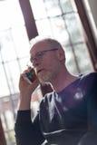 Homem superior que fala no telefone, na luz dura e no efeito do alargamento Fotografia de Stock