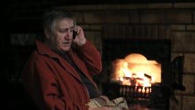 Homem superior que fala pelo telefone celular que senta-se na cadeira na frente da chaminé video estoque