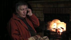 Homem superior que fala pelo telefone celular que senta-se na cadeira perto da chaminé vídeos de arquivo