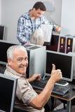 Homem superior que gesticula os polegares acima na mesa do computador imagens de stock