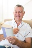Homem superior que guarda o livro e os vidros fotografia de stock royalty free