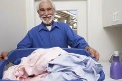 Homem superior que guardara a cesta de lavanderia Fotos de Stock Royalty Free