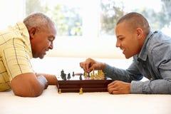Homem superior que joga a xadrez com filho imagens de stock royalty free