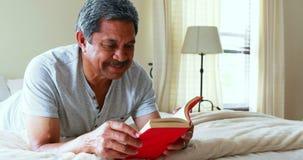 Homem superior que lê um noel no quarto 4k video estoque