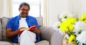 Homem superior que lê uma novela na sala de visitas 4k filme