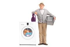 Homem superior que levanta ao lado de uma máquina de lavar Imagens de Stock Royalty Free