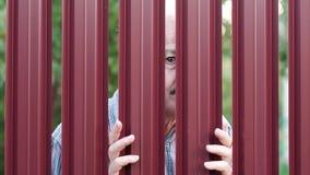 Homem superior que olha através da cerca que espia em seu vizinho vídeos de arquivo