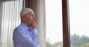 Homem superior que olha através da janela video estoque