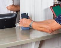 Homem superior que paga com Smartphone no contador foto de stock