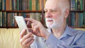 Homem superior que relaxa em casa a notícia de leitura na tabuleta que aprecia a aposentadoria Estantes no fundo vídeos de arquivo