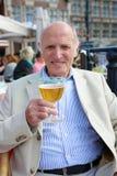 Homem superior que relaxa no café do ar livre com bebida foto de stock royalty free