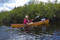 Homem superior que rema uma canoa pequena no rio dos alces fotografia de stock