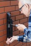 Homem superior que repara o fechamento da porta Imagens de Stock