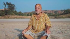Homem superior que senta e que medita sobre o Sandy Beach filme