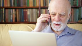 Homem superior que senta-se em casa com portátil e smartphone Usando o telefone celular que discute o projeto na tela filme