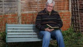 Homem superior que senta-se em um banco e em uma leitura video estoque