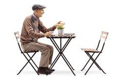 Homem superior que senta-se em um café bebendo da tabela e que gesticula uma conversação imagem de stock