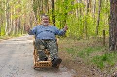 Homem superior que senta-se em uma balançar-cadeira de vime na floresta da mola fotos de stock royalty free