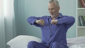 Homem superior que senta-se na borda da cama e que boceja, manhã feliz, completa da energia video estoque
