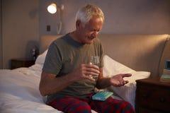 Homem superior que senta-se na cama em casa que toma a medicamentação imagens de stock royalty free