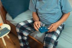 Homem superior que senta-se na cama que pega a medicamentação, fim Foto de Stock Royalty Free