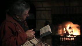 Homem superior que senta-se na chaminé com o livro e que bebe um chá video estoque