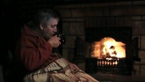 Homem superior que senta-se na chaminé e que bebe um chá vídeos de arquivo