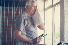 Homem superior que senta-se na máquina do exercício O homem limpa sua cara com imagem de stock