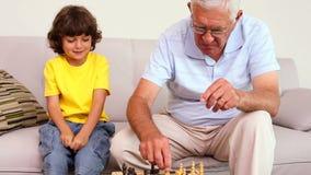 Homem superior que senta-se no sofá com seu neto que joga a xadrez
