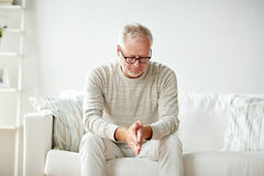 homem superior que senta-se no sofá em casa e no pensamento Imagem de Stock