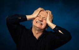 Homem superior que sofre da dor de cabeça imagem de stock
